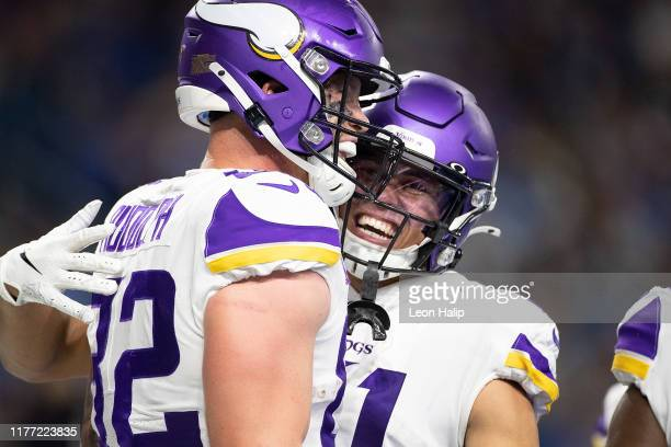 Kyle Rudolph of the Minnesota Vikings celebrates a touchdown with teammate Austin Cutting during the fourth quarter of the game at Ford Field on...