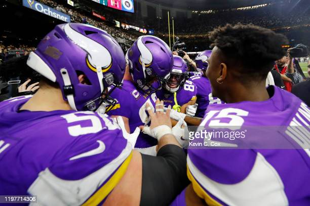 Kyle Rudolph of the Minnesota Vikings celebrates with teammates after catching the game-winning touchdown reception against P.J. Williams of the New...