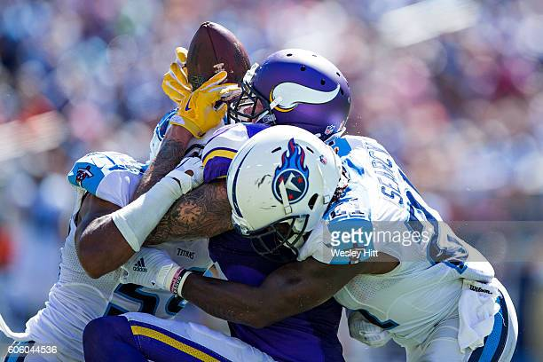Kyle Rudolph of the Minnesota Vikings has a pass knocked away by Sean Spence and Da'Norris Searcy of the Tennessee Titans at Nissan Stadium on...