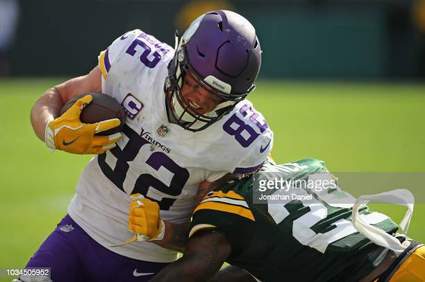 Kyle Rudolph of the Minnesota Vikings is hit by Kentrell Brice of the Green Bay Packers after catching a first down pass at Lambeau Field on...
