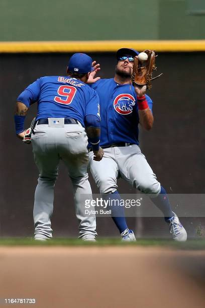Kyle Schwarber of the Chicago Cubs catches a fly ball next to Javier Baez in the sixth inning against the Milwaukee Brewers at Miller Park on July 28...