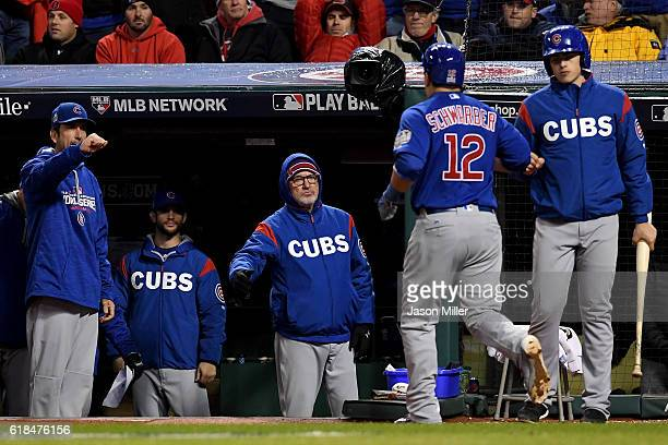 Kyle Schwarber of the Chicago Cubs celebrates at the dugout with manager Joe Maddon after scoring a run during the fifth inning against the Cleveland...