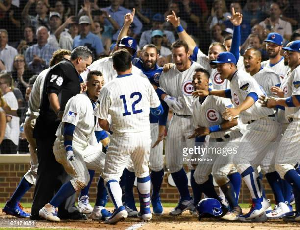 Kyle Schwarber of the Chicago Cubs celebrates his walk off home run against the Cincinnati Reds with his teammates during the tenth inning at Wrigley...