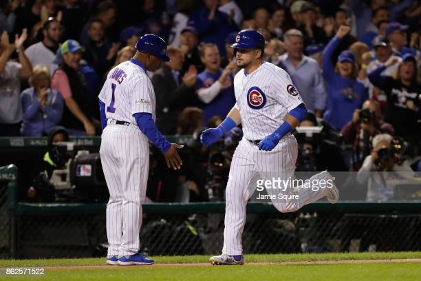 Kyle Schwarber of the Chicago Cubs celebrates with third base coach Gary Jones after hitting a home run in the first inning against the Los Angeles...