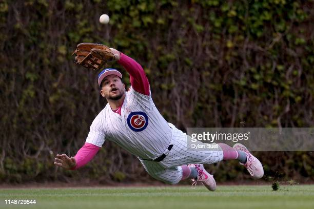 Kyle Schwarber of the Chicago Cubs dives in an attempt to catch a fly ball in the fourth inning against the Milwaukee Brewers at Wrigley Field on May...