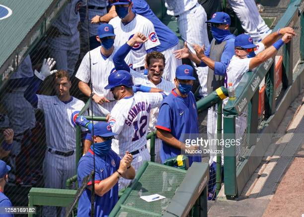Kyle Schwarber of the Chicago Cubs is congratulated by teammates in the dugout following his two run home run against the Milwaukee Brewers during...