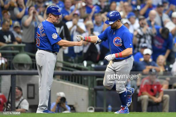 Kyle Schwarber of the Chicago Cubs is congratulated by third base coach Brian Butterfield following a home run against the Milwaukee Brewers during...