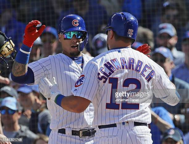 Kyle Schwarber of the Chicago Cubs is greeted by teammate Javier Baez after hitting a two run home run in the 4th inning against the Pittsburgh...