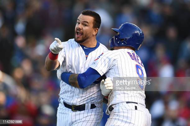 Kyle Schwarber of the Chicago Cubs is restrained by Javier Baez after being called out by the third base umpire during the ninth inning of a game...