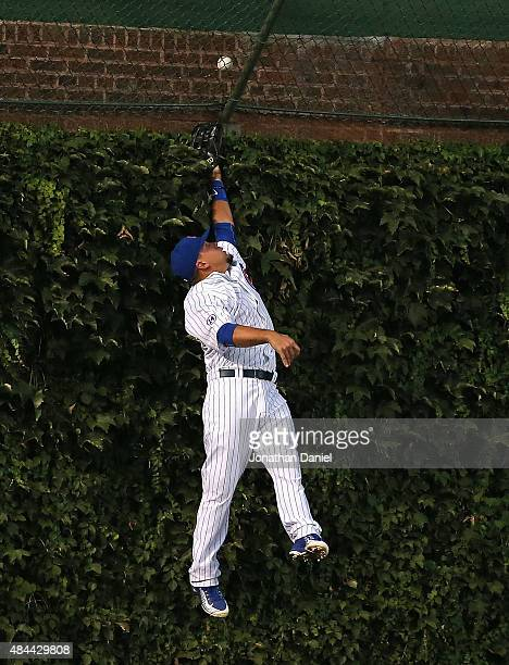 Kyle Schwarber of the Chicago Cubs leaps to try and catch a home run ball hit by In Kinsler of the Detroit Tigers in the 1st inning at Wrigley Field...