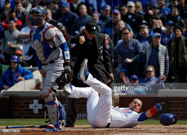 Kyle Schwarber of the Chicago Cubs points to the dugout to call for a replay review after he was tagged out by Yasmani Grandal of the Los Angeles...