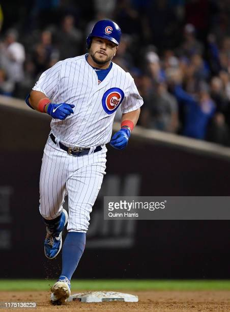 Kyle Schwarber of the Chicago Cubs rounds the bases after his three run home run in the first inning against the Cincinnati Reds at Wrigley Field on...