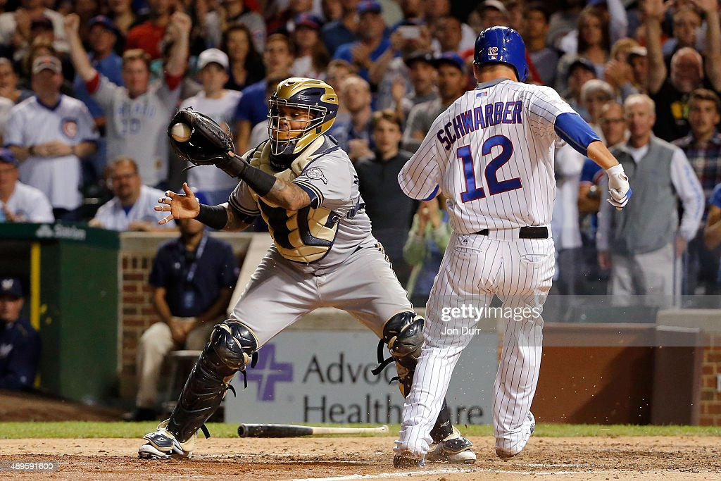 Kyle Schwarber #12 of the Chicago Cubs scores on an RBI double by Kris Bryant #17 (not pictured) as Martin Maldonado #12 of the Milwaukee Brewers takes the throw during the eighth inning at Wrigley Field on September 22, 2015 in Chicago, Illinois.