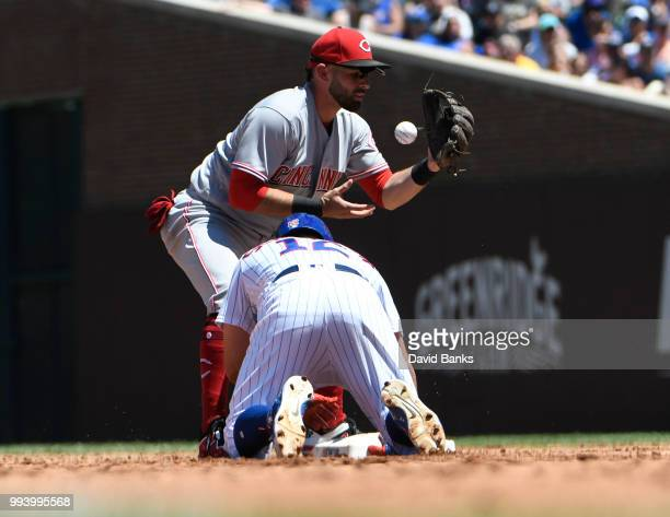 Kyle Schwarber of the Chicago Cubs slides safely back into second base as Jose Peraza of the Cincinnati Reds makes a late tag during the second...