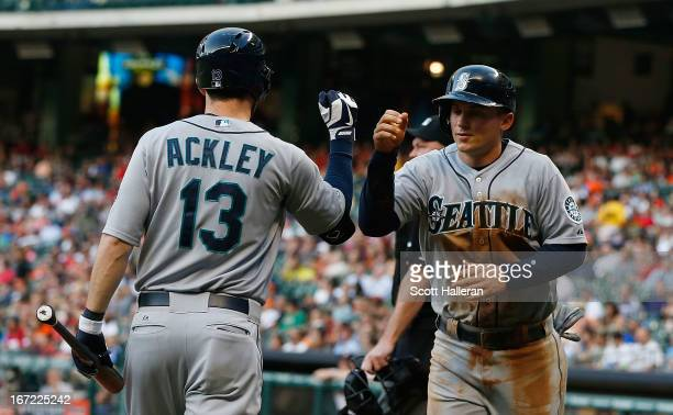 Kyle Seager and Dustin Ackley of the Seattle Mariners celebrate after Seager scored a run in the first inning of the game against the Houston Astros...