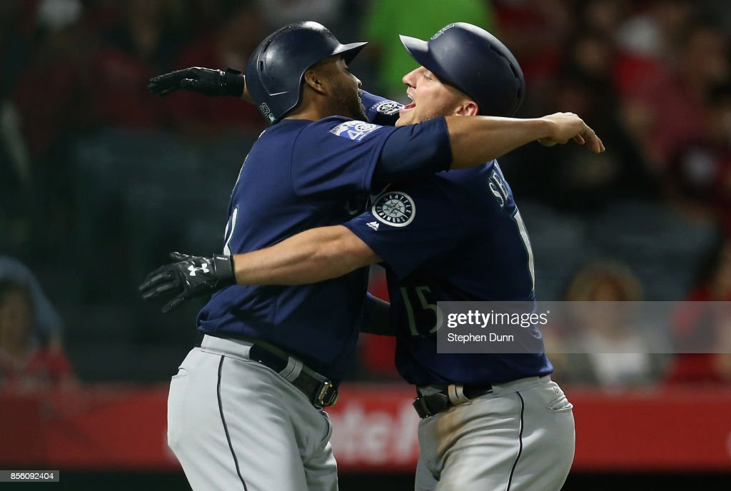 Kyle Seager #15 and Nelson Cruz #23 of the Seattle Mariners celebrate after both score on Seager's three run home run in the eighth inning to give the Mariners the lead against the Los Angeles Angels of Anaheim on September 30, 2017 at Angel Stadium of Anaheim in Anaheim, California.