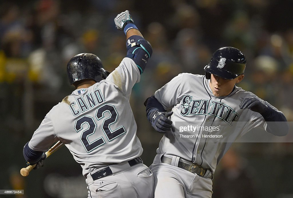 Kyle Seager #15 and Robinson Cano #22 of the Seattle Mariners celebrates after Seager hit a two-run homer against the Oakland Athletics in the top of the ninth inning at O.co Coliseum on September 4, 2015 in Oakland, California. The Mariners won the game 11-8.