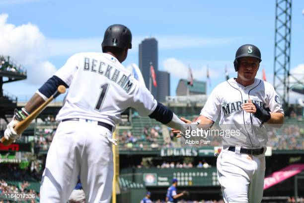 Kyle Seager high fives Tim Beckham after scoring off a single by Austin Nola of the Seattle Mariners in the fifth inning against the Texas Rangers...