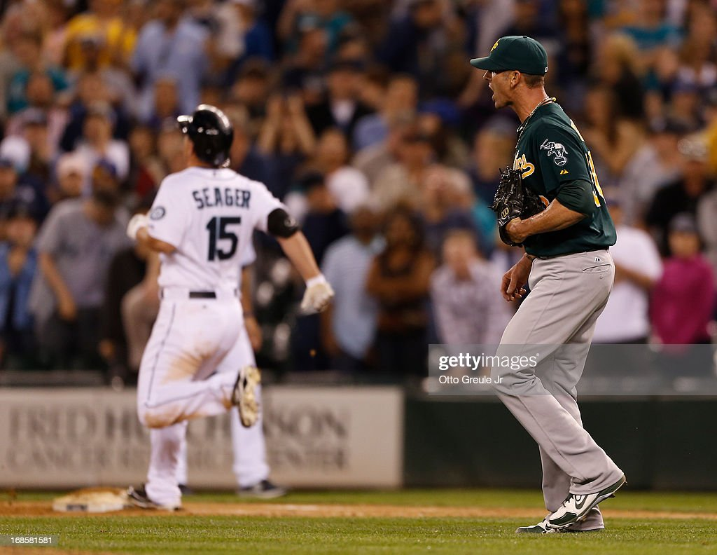 Kyle Seager #15 of the Seattle Mariners grounds out with the bases loaded to end the game as closing pitcher Grant Balfour #50 of the Oakland Athletics looks on at Safeco Field on May 11, 2013 in Seattle, Washington.
