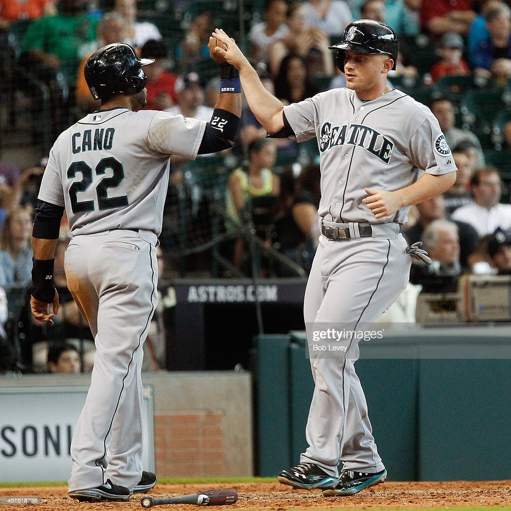 Kyle Seager #15 of the Seattle Mariners high fives Robinson Cano #22 after they scored on a double by Logan Morrison #20 in the sixth inning against the Houston Astros at Minute Maid Park on July 2, 2014 in Houston, Texas.