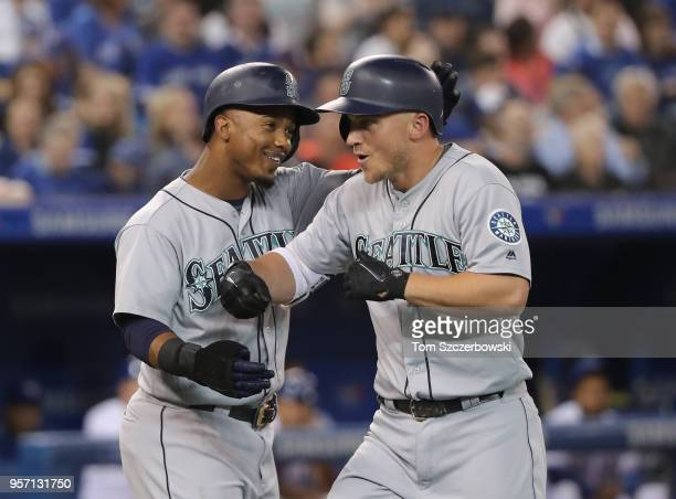 Kyle Seager of the Seattle Mariners is congratulated by Jean Segura after hitting a grand slam home run in the first inning during MLB game action...