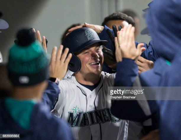 Kyle Seager of the Seattle Mariners is congratulated by teammates in the dugout after hitting a solo home run off of relief pitcher Ryan Madson of...