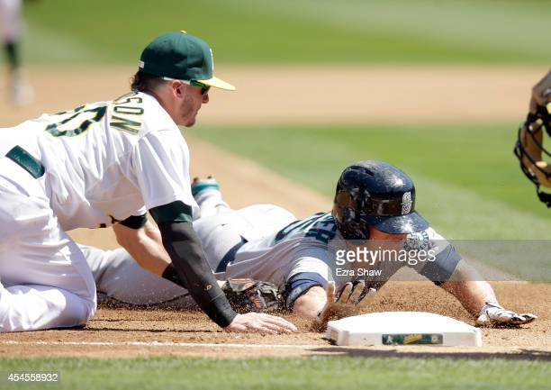 Kyle Seager of the Seattle Mariners is tagged out by Josh Donaldson of the Oakland Athletics when he tried to strech a hit into a triple in the...