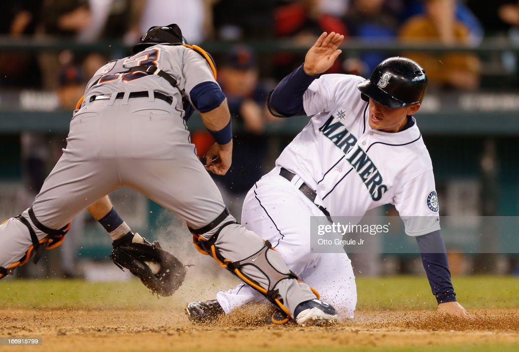 Kyle Seager #15 of the Seattle Mariners scores on an RBI single by Endy Chavez against catcher Alex Avila #13 of the Detroit Tigers in the seventh inning at Safeco Field on April 18, 2013 in Seattle, Washington.