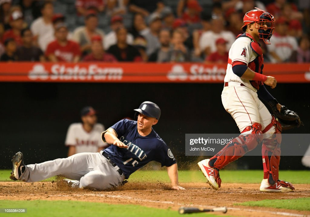 Kyle Seager #15 of the Seattle Mariners slides past Jose Briceno #10 of the Los Angeles Angels of Anaheim safe on a two rbi single by Dee Gordon in the seventh inning at Angel Stadium on September 14, 2018 in Anaheim, California.