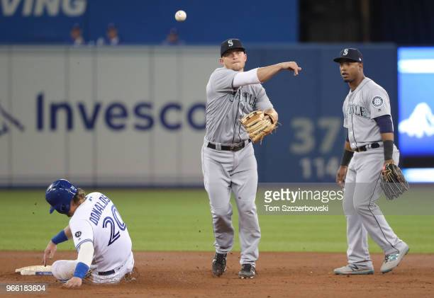 Kyle Seager of the Seattle Mariners turns a double play as Jean Segura watches in the third inning during MLB game action as Josh Donaldson of the...