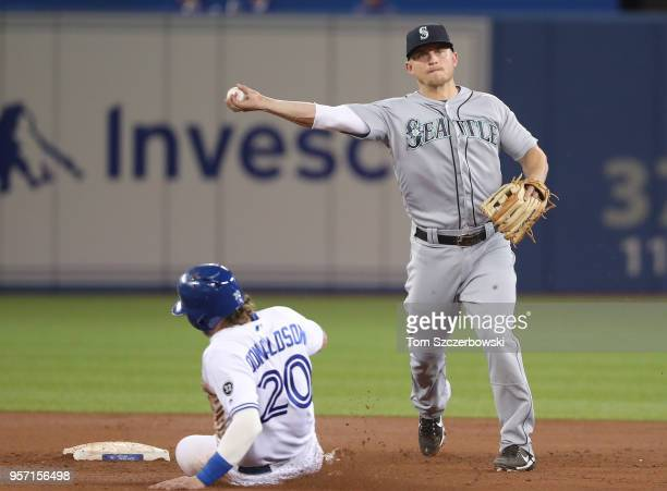 Kyle Seager of the Seattle Mariners turns a double play in the third inning during MLB game action as Josh Donaldson of the Toronto Blue Jays slides...