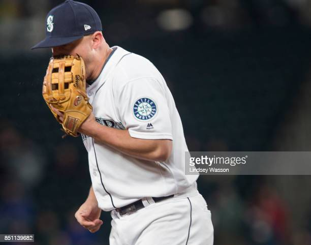 Kyle Seager of the Seattle Mariners yells into his glove after committing an error in the seventh inning allowing shortstop Elvis Andrus of the Texas...