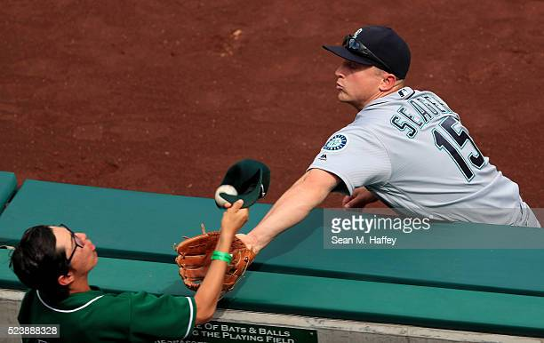 Kyle Seager of the the Seattle Mariners is unable to reach a foul ball hit by Mike Trout of the the Los Angeles Angels of Anaheim as a fan tries to...
