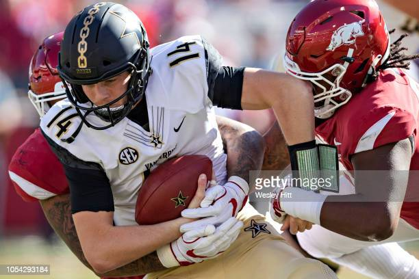 Kyle Shurmur of the Vanderbilt Commodores is sacked in the first half of the game by Armon Watts of the Arkansas Razorbacks at Razorback Stadium on...