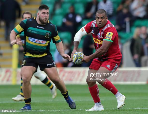Kyle Sinckler of Harlequins passes the ball watched by Kieran Brookes during the Aviva Premiership match between Northampton Saints and Harlequins at...