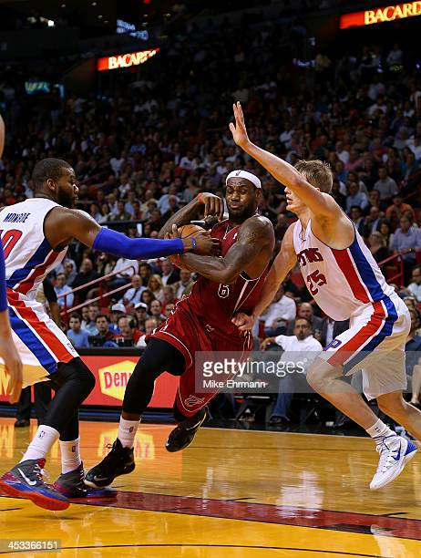 Kyle Singler and Greg Monroe of the Detroit Pistons guard LeBron James of the Miami Heat during a game at American Airlines Arena on December 3 2013...