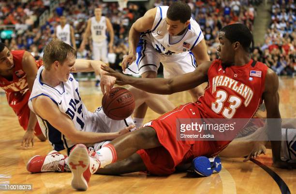 Kyle Singler of the Duke Blue Devils and Dino Gregory of the Maryland Terrapins battle for possession of the ball during the second half in the...