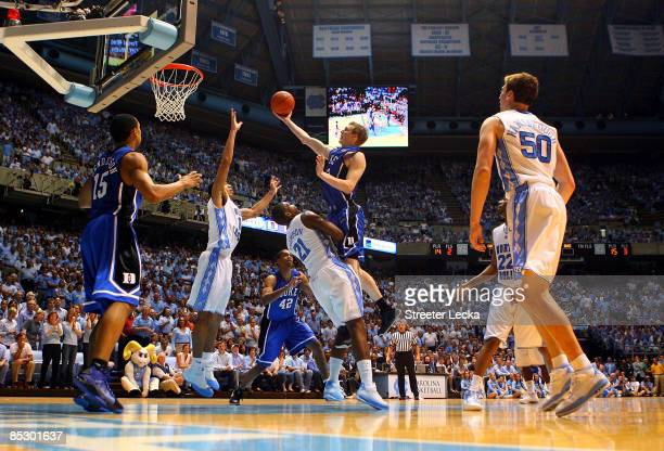 Kyle Singler of the Duke Blue Devils charges over Deon Thompson of the North Carolina Tar Heels during their game at the Dean E. Smith Center on...