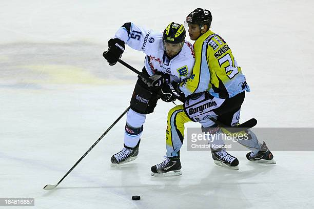 Kyle Sonnenburg of Krefeld Pinguine uses his stick against John Laliberte of ERC Ingolstadt during the fifth DEL PlayOffmatch between Krefeld...