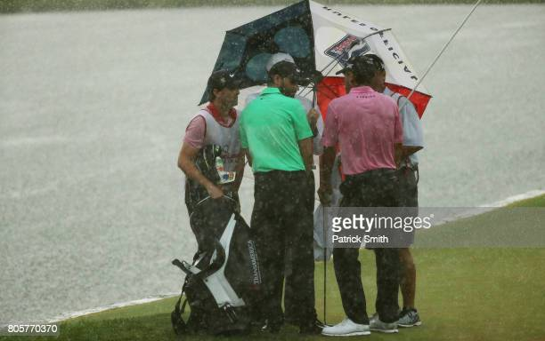 Kyle Stanley of the United States and Charles Howell III of the United States take cover during a rainstorm during the final round of the Quicken...