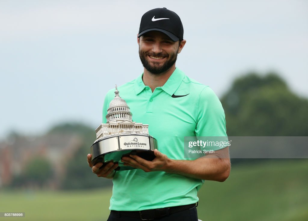 Kyle Stanley of the United States celebrates with the winner's trophy after defeating Charles Howell III of the United States during a playoff in the final round of the Quicken Loans National on July 2, 2017 TPC Potomac in Potomac, Maryland.