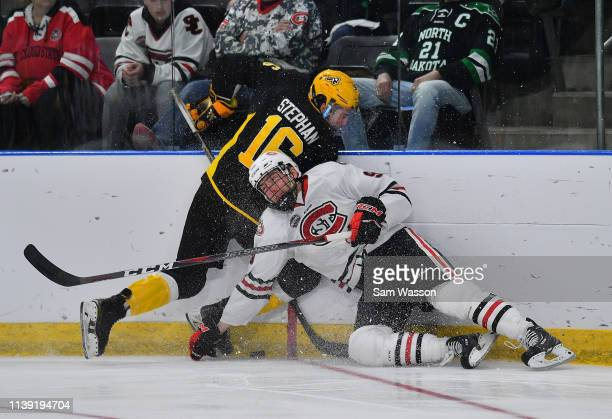 Kyle Stephan of the American International Yellow Jackets and Spencer Meier of the St Cloud State Huskies battle for the puck during an NCAA Division...