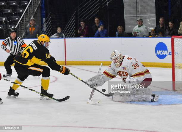 Kyle Stephan of the American International Yellow Jackets shoots the puck against Filip Larsson of the Denver Pioneers during the NCAA Division I...