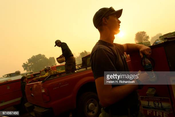 Kyle Swanstrom right a firefighter with a Type II hand crew with Idaho Department of Lands chats with members of his crew after gearing up before...