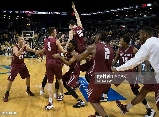 Kyle Thompson Lamarr Kimble Mike Booth DeAndre Bembry and Aaron Brown of the Saint Joseph's Hawks celebrate after the game against the Virginia...