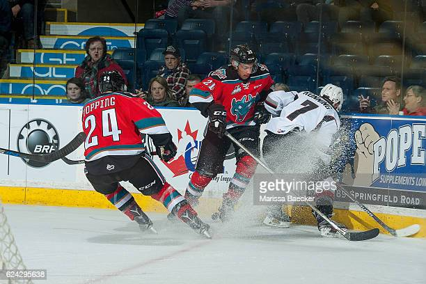 Kyle Topping and Devante Stephens of the Kelowna Rockets check Ty Ronning of the Vancouver Giants at the boards during second period on November 18...