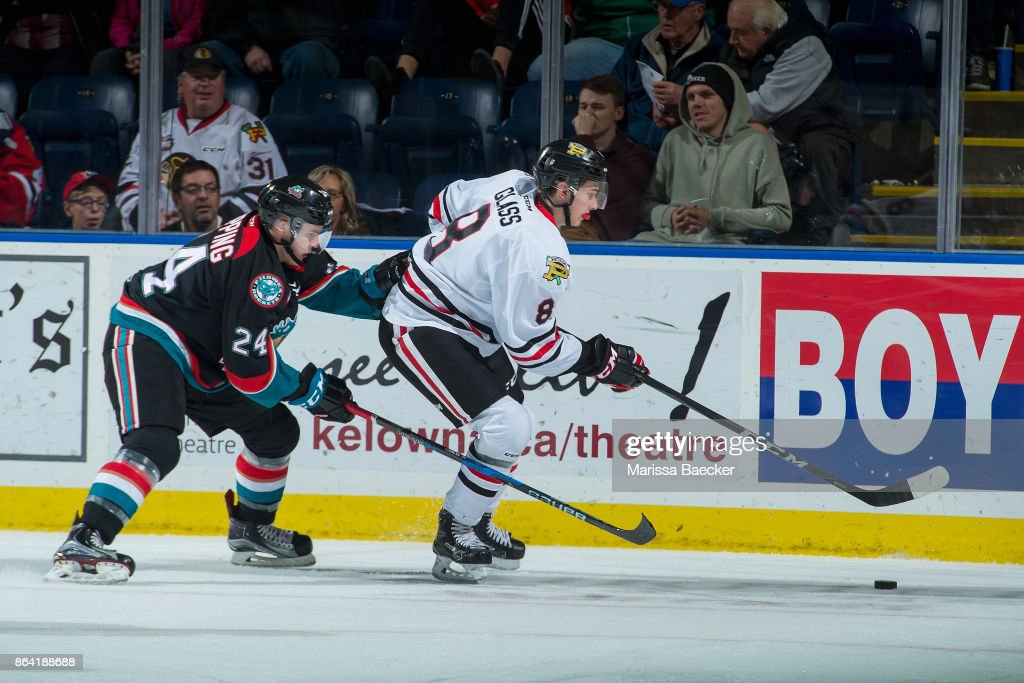 Kyle Topping #24 of the Kelowna Rockets back checks Cody Glass #8 of the Portland Winterhawks as he skates with the puck during third period at Prospera Place on October 20, 2017 in Kelowna, Canada.