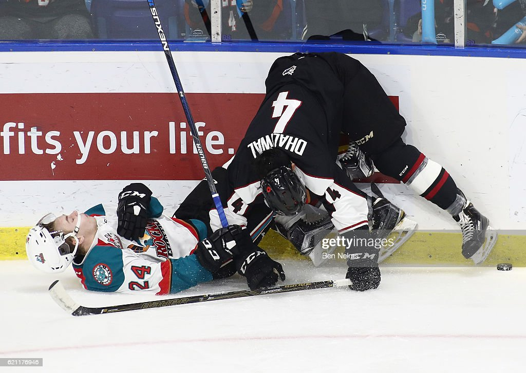 Kyle Topping #24 of the Kelowna Rockets is checked by Bailey Dhaliwal #4 of the Vancouver Giants during the first period of their WHL game at the Langley Events Centre on November 4, 2016 in Langley, British Columbia, Canada.