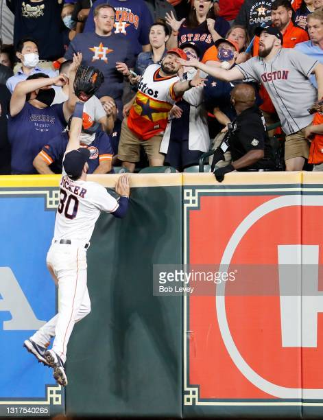 Kyle Tucker of the Houston Astros attempts to make a catch on a home run by Taylor Ward of the Los Angeles Angels in the eighth inning at Minute Maid...