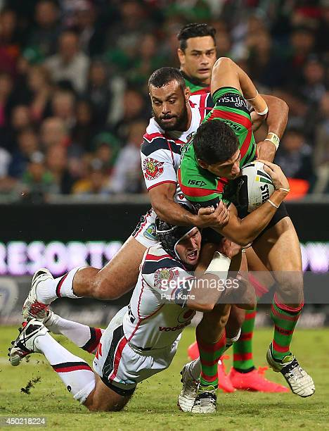 Kyle Turner of the Rabbitohs is tackled by Nathan Friend and Jayson Bukuya of the Warriors during the round 13 NRL match between the South Sydney...